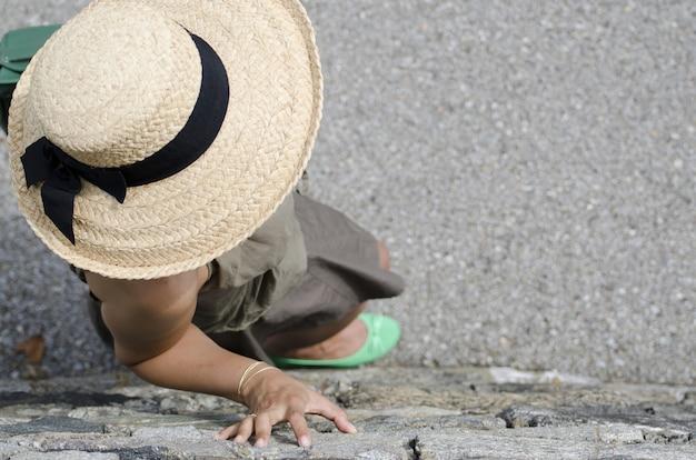 麦わら帽子と緑の靴が壁に寄りかかっている女性のハイアングルショット 無料写真