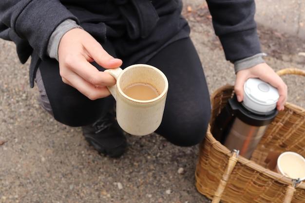 一杯のコーヒーとフラスコを保持しているハイカーのハイアングルショット 無料写真