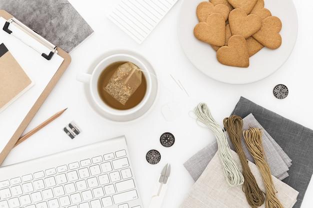 キーボード、一杯のお茶とクッキー、いくつかの糸と白い表面上の紙のハイアングルショット 無料写真