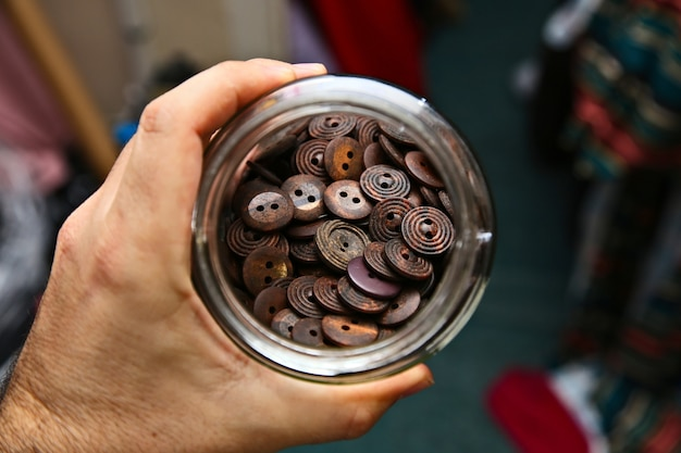 茶色のボタンでいっぱいの瓶を持っている人のハイアングルショット 無料写真