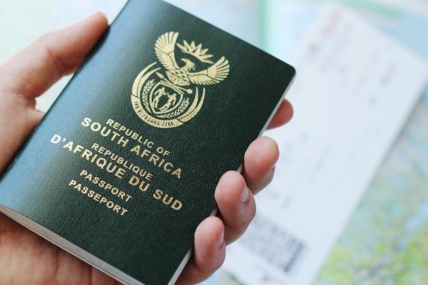 Снимок с высоким углом человека, держащего паспорт над билетом на самолет и географической картой Бесплатные Фотографии