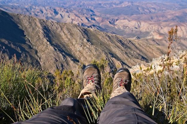 美しい渓谷の丘の上に座っている人の足のハイアングルショット 無料写真
