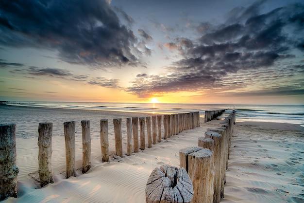일몰 바다로 이어지는 해안에 나무 갑판의 높은 각도 샷 무료 사진