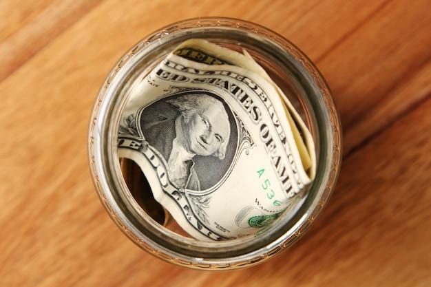 木製の表面にガラスの瓶にアメリカのドル札のハイアングルショット 無料写真