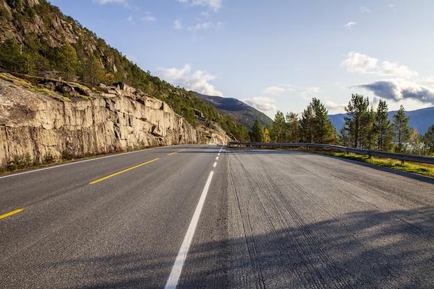 木々や丘に囲まれたノルウェーの空の道のハイアングルショット 無料写真