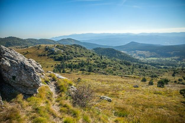 スロベニアの青い空の下に森のある美しい山々のハイアングルショット 無料写真