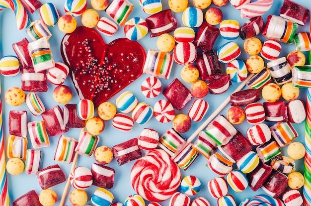 カラフルなキャンディーとハート型のロリポップのハイアングルショット-クールな壁紙に最適 無料写真