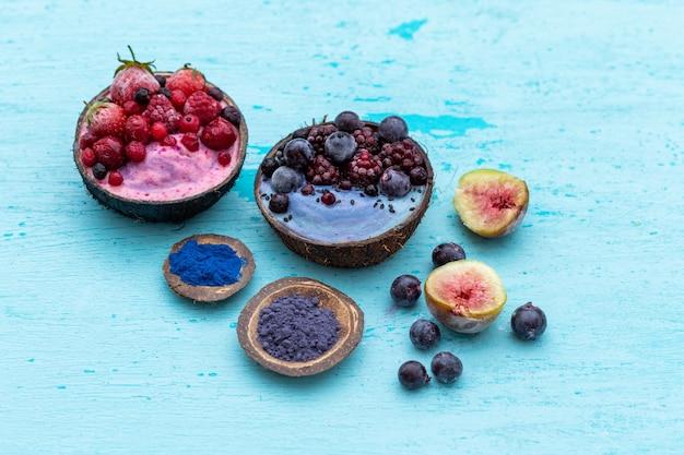 ココナッツボウルに冷凍フルーツをトッピングしたおいしいフルーツシェイクのハイアングルショット 無料写真