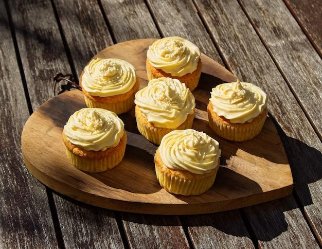 나무 표면에 맛있는 달콤한 버터 크림 컵 케이크의 높은 각도 샷 무료 사진