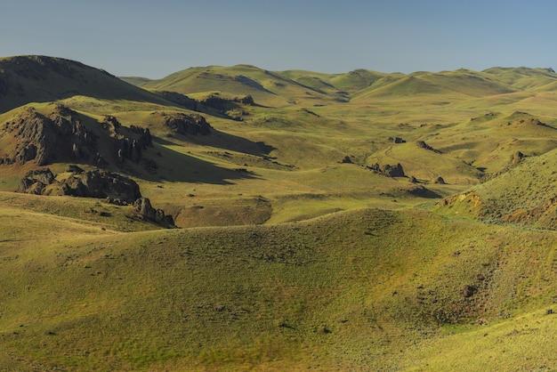 昼間の背景に青い空と空の草が茂った丘のハイアングルショット 無料写真