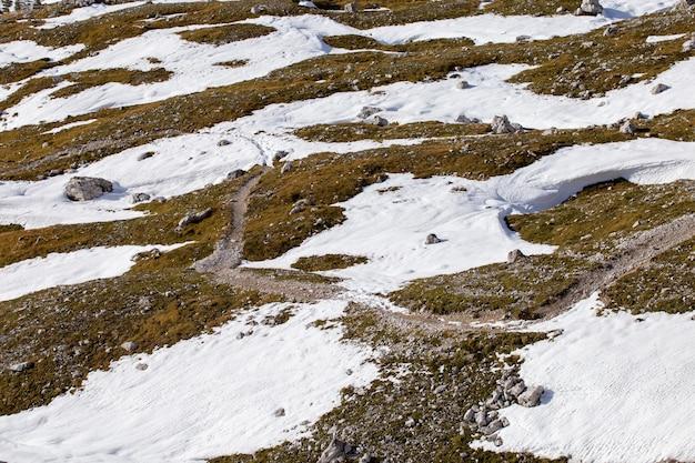 Высокий угол выстрела текстуры земли частично покрыты снегом в итальянских альпах Бесплатные Фотографии