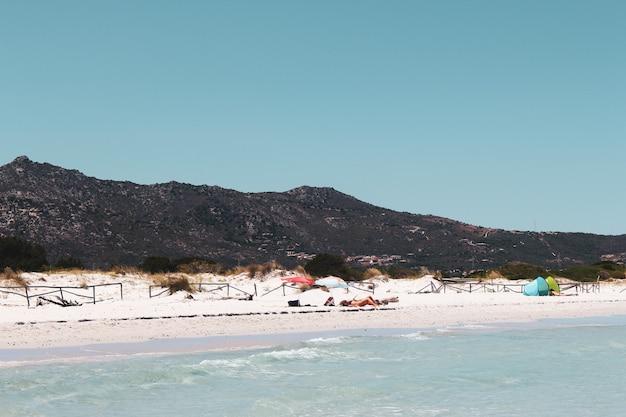 サルデーニャ島サンテオドーロのビーチでリラックスしている人々のハイアングルショット 無料写真