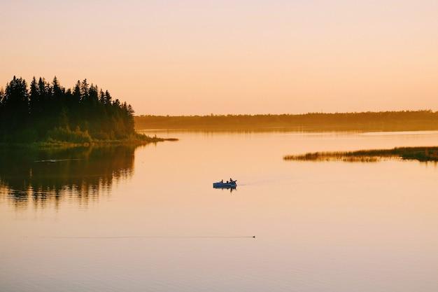 日没時に湖でボートに乗って航海する人々のハイアングルショット 無料写真