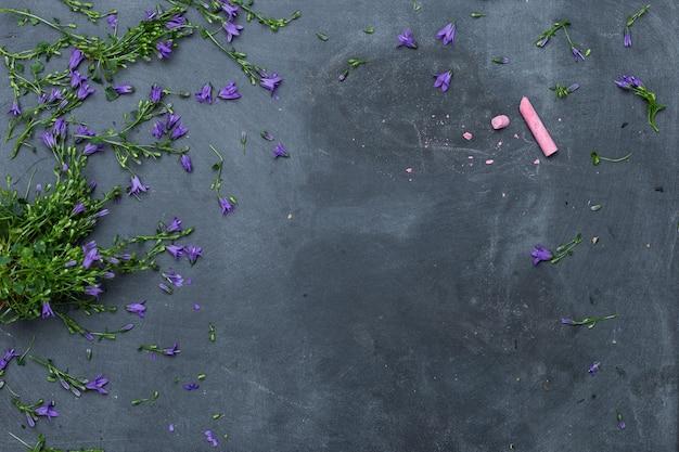 ピンクのチョークで黒い表面に広がる紫色の花のハイアングルショット 無料写真