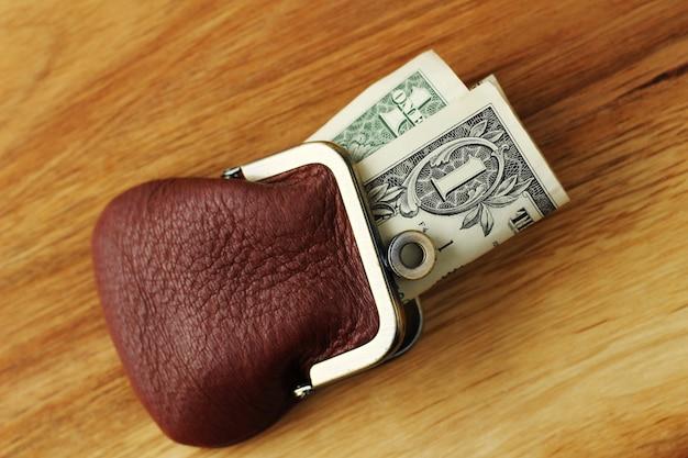Снимок денег в кожаном портмоне на деревянной поверхности под высоким углом Бесплатные Фотографии