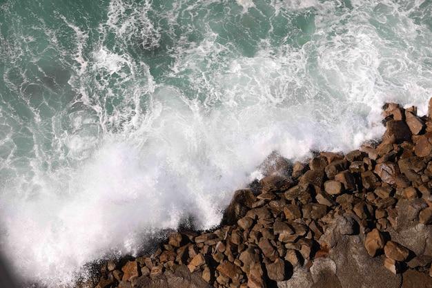 Высокий угол обзора воды, плещущейся на пляжных скалах Бесплатные Фотографии