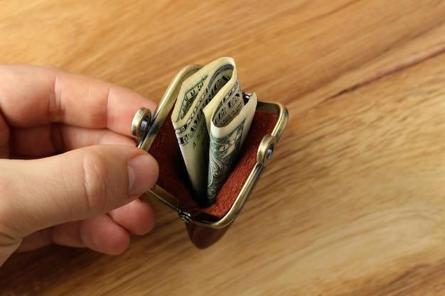 Colpo di alto angolo di una persona in possesso di un portamonete con dei contanti su una superficie di legno Foto Gratuite