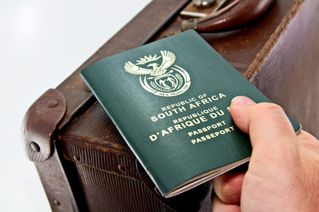 High angle shot of a person holding a passport over a leather suitcase with a white Free Photo