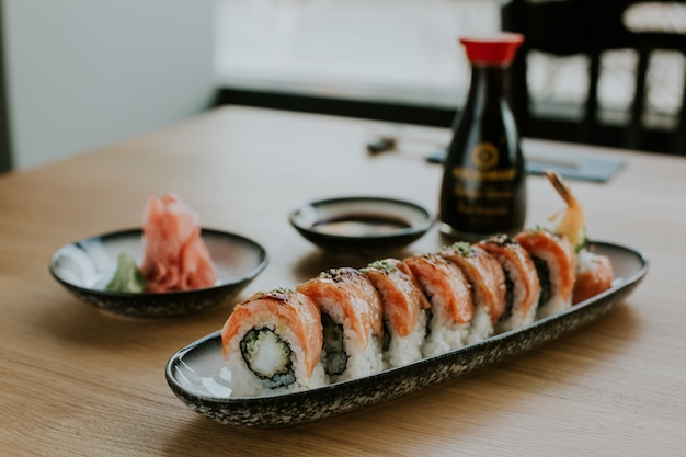 High angle shot of a plate with sushi and its ingredients on a table Free Photo