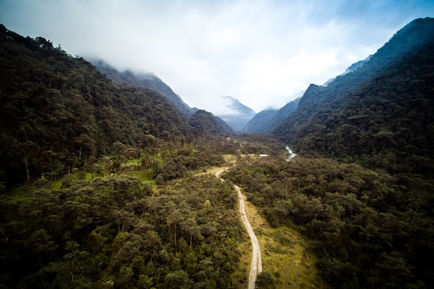 High angle shot of a road surrounded by green trees and mountains with a cloudy sky Free Photo