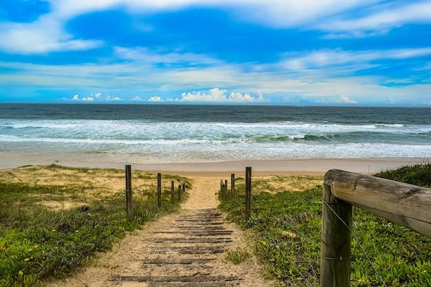 Colpo di alto angolo di una strada con ringhiere in legno che portano al mare Foto Gratuite
