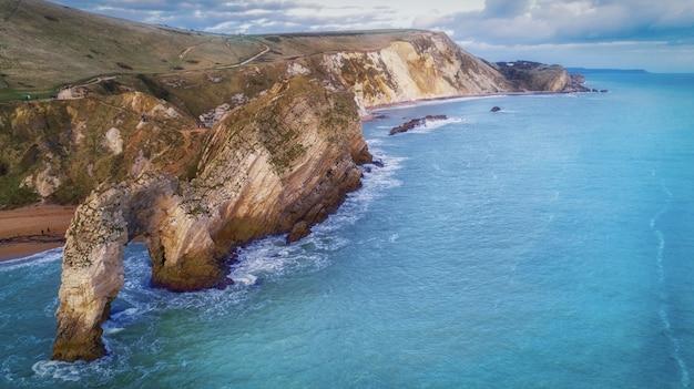 Colpo di alto angolo delle rocce in riva al mare del durdle door nel dorset Foto Gratuite