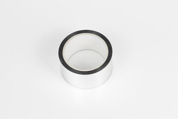 Colpo di alto angolo di un rotolo di nastro d'argento su una superficie grigia Foto Gratuite