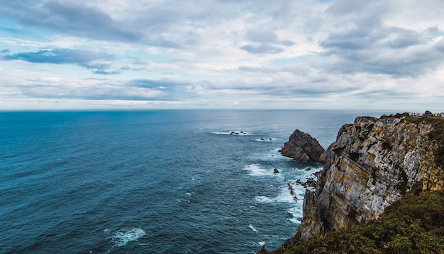 High angle shot of the sea near the mountain under a cloudy sky in cabo penas, asturias, spain Free Photo