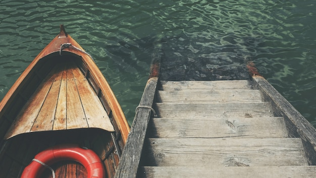 High angle shot of a small boat near the wooden stairs in the beautiful sea Free Photo