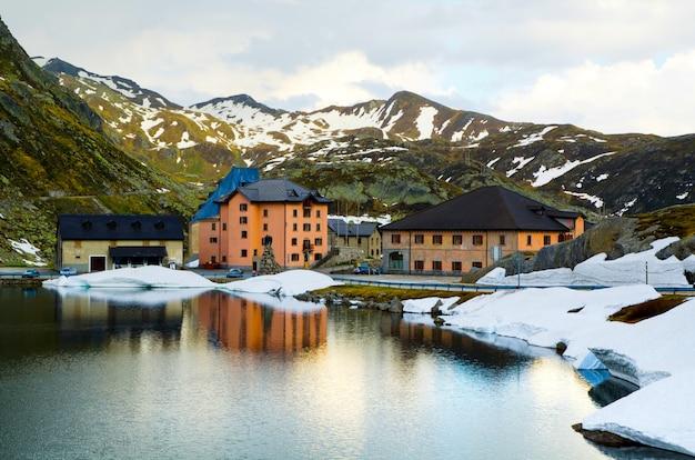 Colpo di alto angolo di alcune case da un lago vicino alle montagne innevate Foto Gratuite