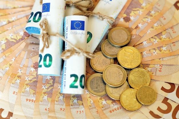 Colpo di alto angolo di alcune banconote e monete arrotolate su più banconote Foto Gratuite