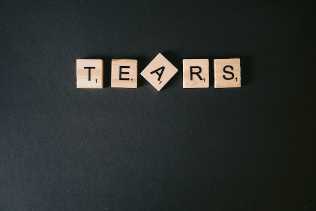 High angle shot of tears message on a black wall Free Photo