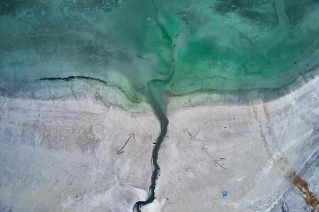 Colpo alto angolo di acqua turchese del mare vicino alla riva con incisioni di frecce Foto Gratuite