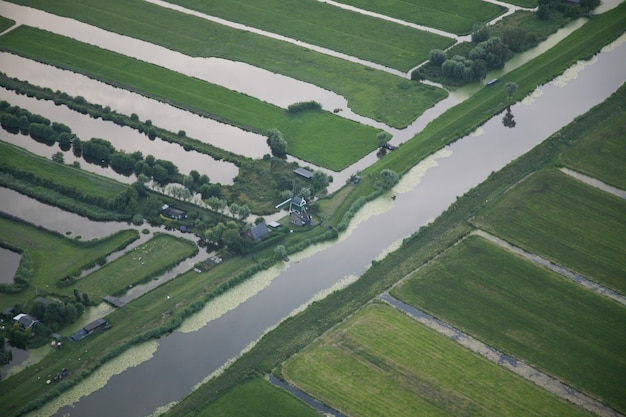 High angle shot of a water stream in the middle of grassy field at dutch polder Free Photo