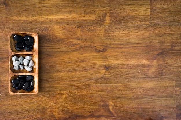Colpo di alto angolo di rocce bianche e nere in un piatto di legno su una superficie di legno Foto Gratuite