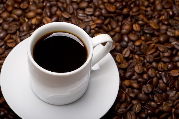 High angle shot of a white cup of black coffee on a surface full of coffee beans Free Photo