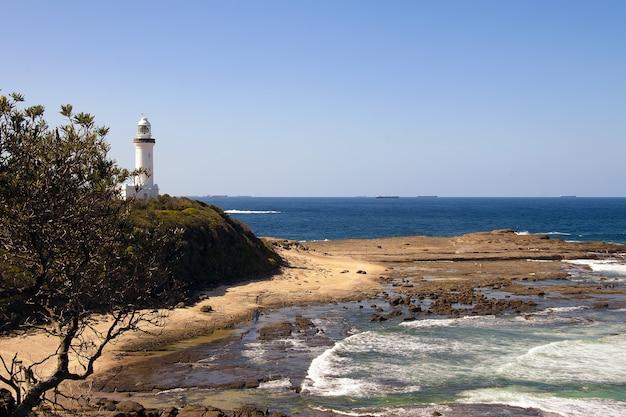 Colpo di alto angolo di un faro bianco sulla riva del mare Foto Gratuite
