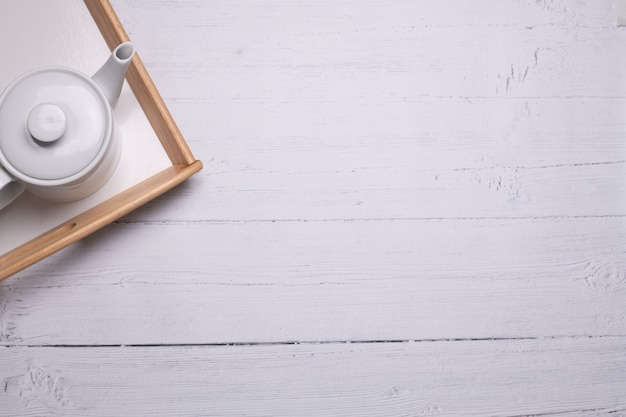High angle shot of a white teapot on a tray on a white wooden table Free Photo