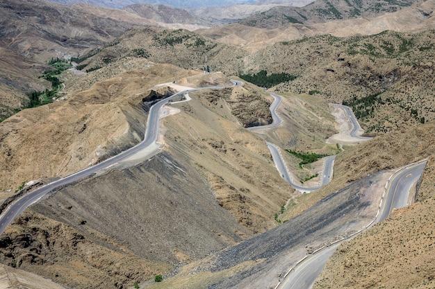 Colpo alto angolo di autostrade tortuose in una zona con colline vuote Foto Gratuite
