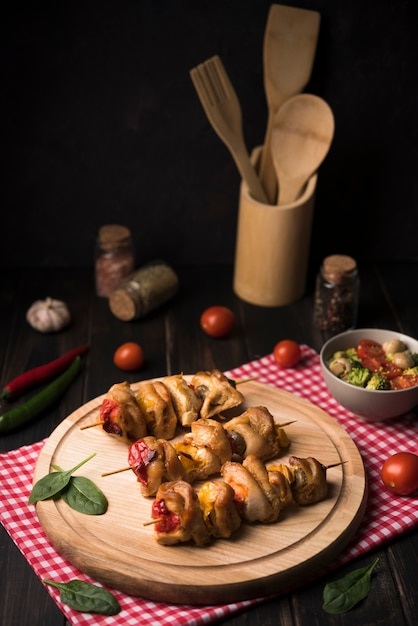 High angle skewers on wooden board with tomatoes Free Photo