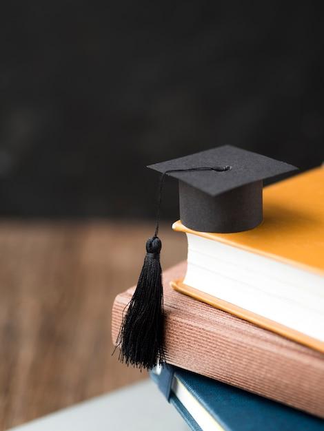 本の山に高角度の小さな卒業の帽子 Premium写真