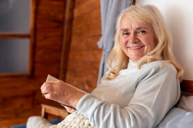 High angle smiley elder woman reading Free Photo