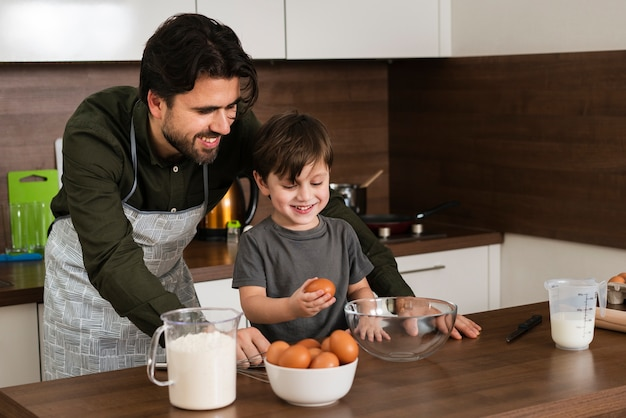 High angle smiley father and son cooking Free Photo