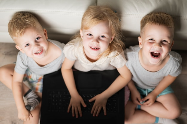 High angle smiley siblings playing on laptop Free Photo