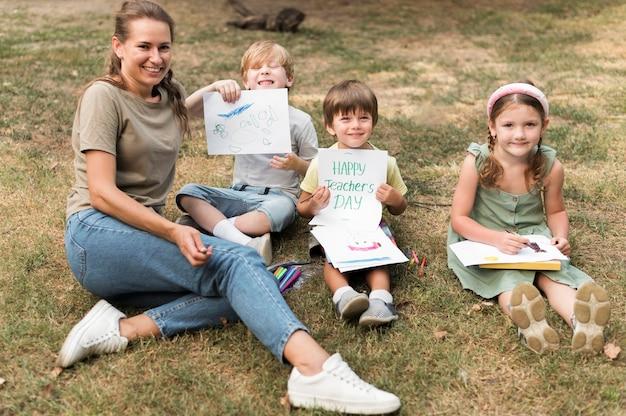 Учитель смайлик под высоким углом и дети на открытом воздухе Бесплатные Фотографии