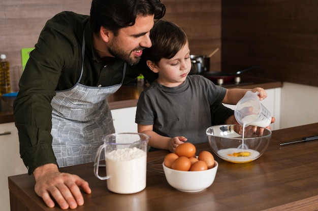 High angle son and father making dough Free Photo