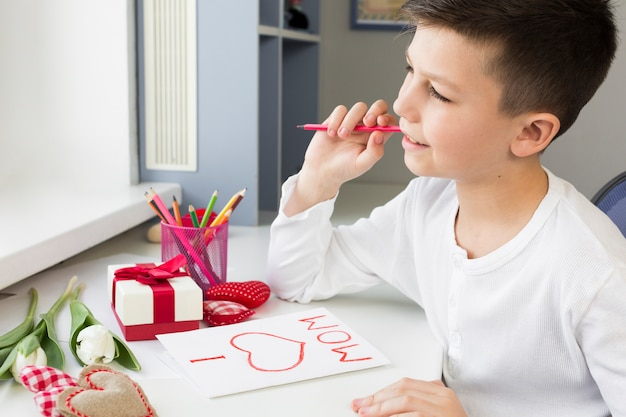 High angle son writing card for his mother Free Photo