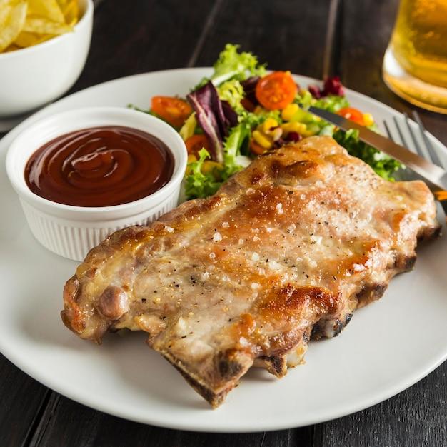 Alto angolo di bistecca sul piatto con birra e salsa Foto Gratuite