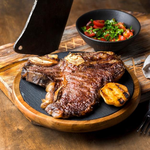 Alto angolo di bistecca sul piatto con insalata e mannaia Foto Gratuite