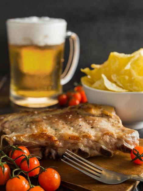 Alto angolo di bistecca con birra e patatine Foto Gratuite